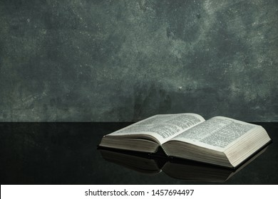 Bible on a black glass table. Beautiful gray wall background