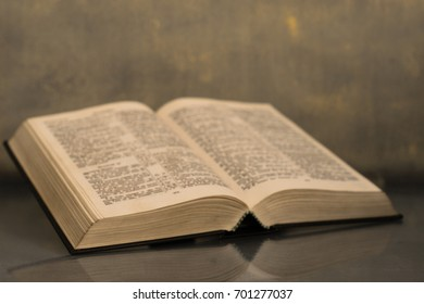 Bible on a glass dark table. Beautiful gold background.Religion concept.