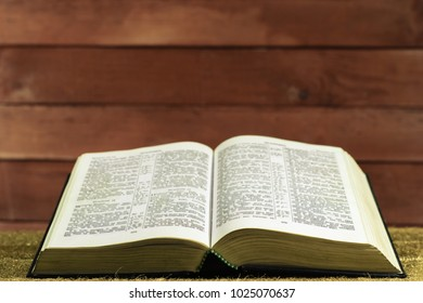 Bible on a Gold table. Beautiful red wooden background.Religion concept.
