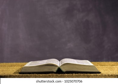 Bible on a gold table. Beautiful dark background.Religion concept.