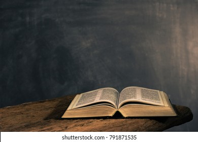 Bible on a old oak wooden table. Beautiful dark background.Religion concept
