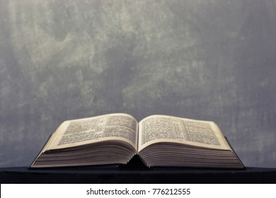 Bible on a round dark table. Beautiful background.Religion concept.