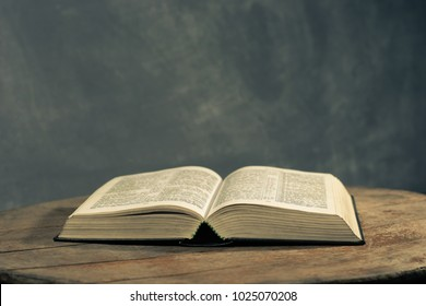 Bible on a round old wood table. Beautiful dark background. Religious concept.