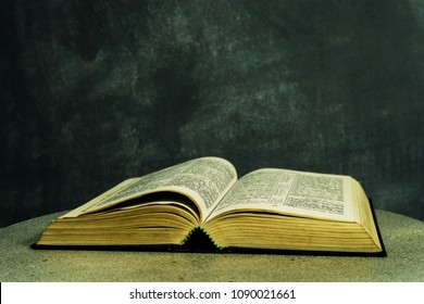 Bible on a round white table. Beautiful dark background. Religious concept.