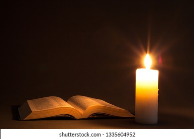bible on the table in the light of a candle