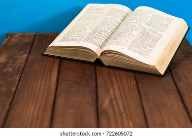Bible on a wooden brown table. Beautiful blue background.Religion concept.