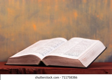 Bible on a wooden red table. Beautiful gold background.Religion concept.