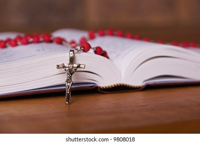 A bible open on a table with a red rosary place ontop of it. Focus on the cross. Perfect for an easter or christmas theme.