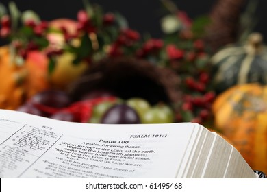 Bible open to Psalm 100 with thanksgiving text and cornucopia in background.