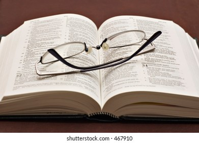 Bible opened with reading glasses
