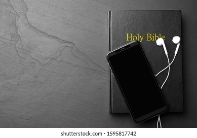Bible, phone and earphones on black background, top view with space for text. Religious audiobook