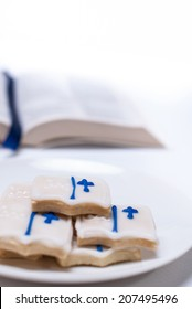 Bible shaped cookies on white plate, bible in background. Shot with copy space.