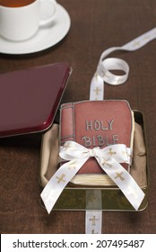 Bible shaped cookies in tin gift box with ribbon and cup of tea. Brown background. Shot with copy space.