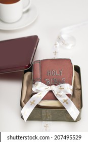 Bible shaped cookies in tin gift box with ribbon and cup of tea. White background. Shot with copy space.