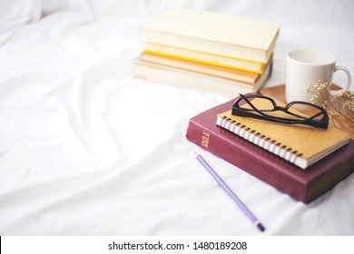 ้Holy bible with small note book, eye glasses, pencil and a cup of black coffee over blurred book stack on bed, Christian background morning devotional concept with copy space