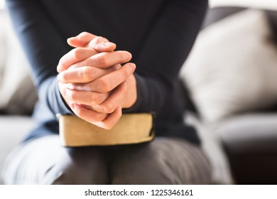 Bible study and Christian faith concept - closeup shot of a woman holding her hands together and praying with a Bible in her lap.