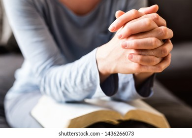 Bible study and faith concept - closeup shot of a woman holding her hands together and praying over an open Bible.