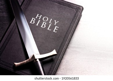 Bible and a Sword on a Dark Wooden Table