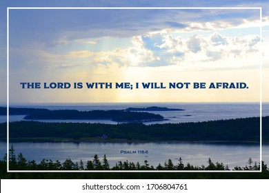 """Bible verse: Psalm 118:6 """"The Lord is with me; I will not be afraid."""" Mountain top view of ocean and islands below with sun rays from behind clouds onto water."""