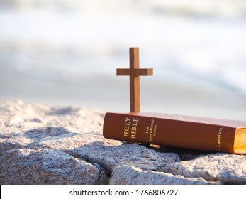 Bible and wood holy cross with blue sea as background. Faith in God. Pray for you. Miracle from heaven. Believe in goddess.Love study bible.Holy book, book of life, Christian background concept.