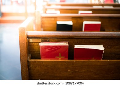 Bibles in wooden bench compartment in church, church service for Christian
