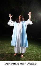 Biblical man wearing white robe and over cloak bathed in light praising and glorifying God. From (Psalm 29:2) Give unto the Lord the glory due unto his name; worship the Lord in the beauty of holiness