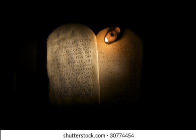 Biblical Ten Commandments inscribed on stone tablets in the Paleo-hebrew script with ancient oil lamp