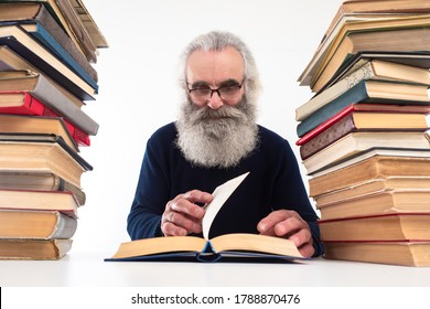 Bibliophile. A man is sitting at a table with stacks of books. A gray-haired man reads a book. A bearded man with glasses likes to read.