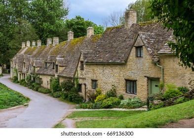 Bi-bury village in Cotswold, small brick houses close to each other with small road and trees