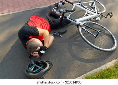 Bicycle accident. Biker lying on the road and holding his head