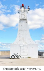 Bicycle against a concrete pier lighthouse, blue sky with fluffy cumulus clouds and blue water in the background.