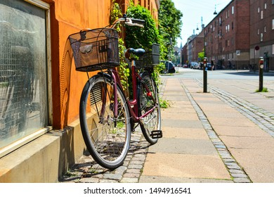 Bicycle with basket in front of the orange wall in Copenhagen, Denmark. Colorful old town architecture. Copenhagen style, European street, Denmark bicycle