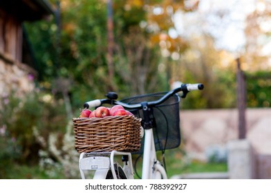 Bicycle with a basket full of apples