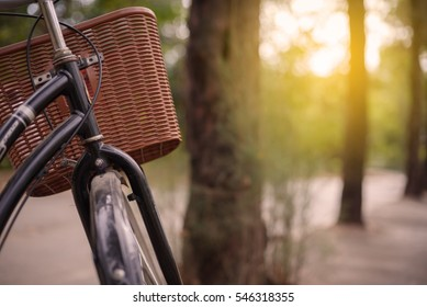 The bicycle with black color on street in the park and sun flare at the destination.