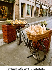 A bicycle with bread baskets stands at a store in the street of the Italian city of Ferrara Italy 28.12.2017 Blurred background