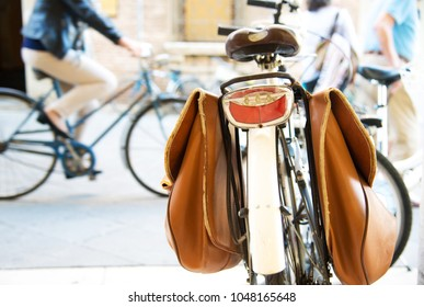 Bicycle  with brown leather panniers (bags)  for luggage parking on the street.Bike riders on background. Selective focus and blur focus.  Italy