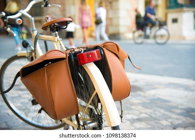 Bicycle with brown pannier bags  parking on the street, people on background.  Street photo. Italian lifestyle. Selective focus on foreground.  Italy, Rimini.