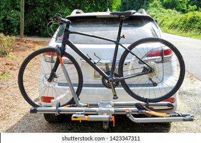 Bicycle in a carrier on back of a car.