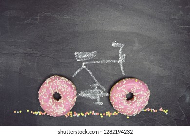 A bicycle with chalk painted on a dark stone surface with pink donuts with white sprinkles as wheels - Abstract concept with donuts as wheels of a bicycle