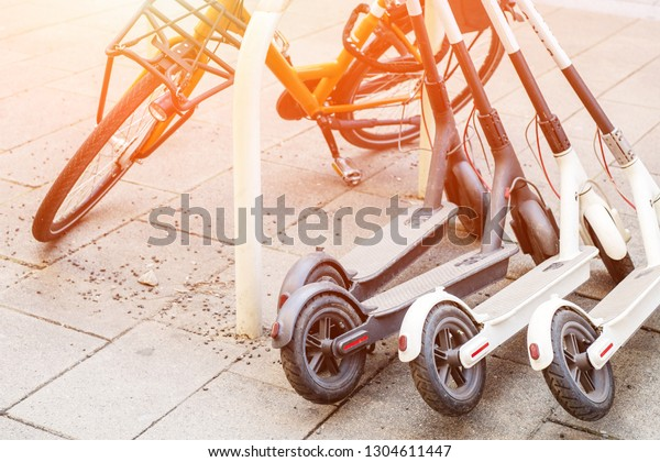Bicycle and electric scooters parked on city street. Self-service street transport rental service. Rent urban vehicle with smartphone application. Zero emission green eco energy