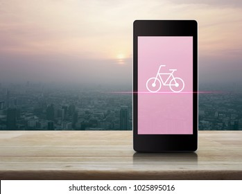 Bicycle flat icon on modern smart phone screen on wooden table over city tower at sunset, vintage style, Bike shop online concept