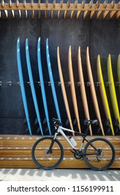 A bicycle in front of a group of surfboards for rent in a surf shop