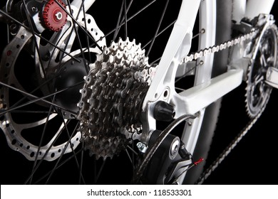 Bicycle gears, disc brake and rear derailleur. Studio shot on black background