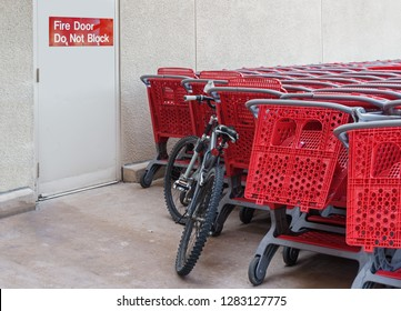 A bicycle and group of red plastic shopping carts stacked near outdoor fire escape door. Sign with words fire door do not block.