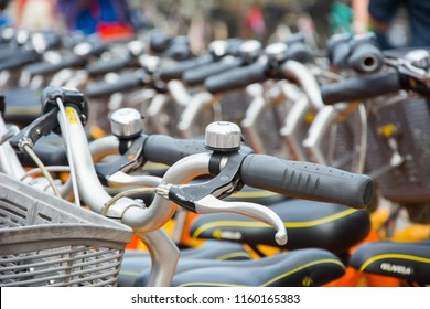 Bicycle handle bar close up.Row of parked vintage bicycles bikes for rent on sidewalk. City bikes