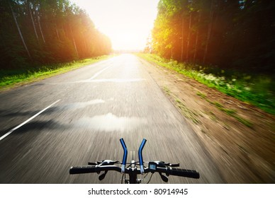 Bicycle handlebar and motion blurred asphalt road through a forest