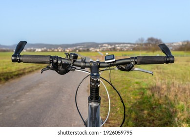A bicycle handlebar seen from the first person perspective. Visible bicycle frame and bicycle accessories on the handlebar, and the road in the background.