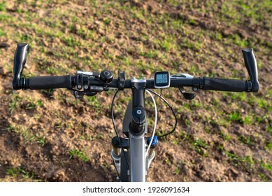 A bicycle handlebar seen from the first person perspective. Visible bicycle frame and bicycle accessories on the handlebar and the field in the background.