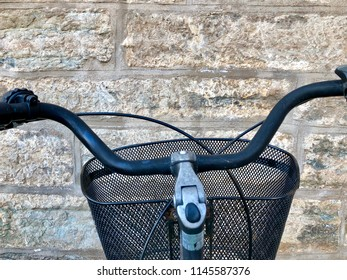 Bicycle handlebars and basket in black and metal silver, against stone brick wall in sandy tones.