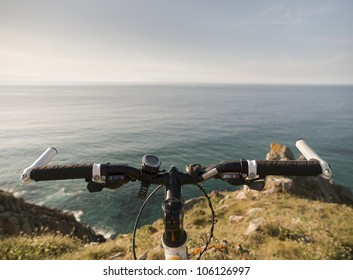 Bicycle handlebars and a coastal landscape. This photo shows the handle in the foreground and background, the sea